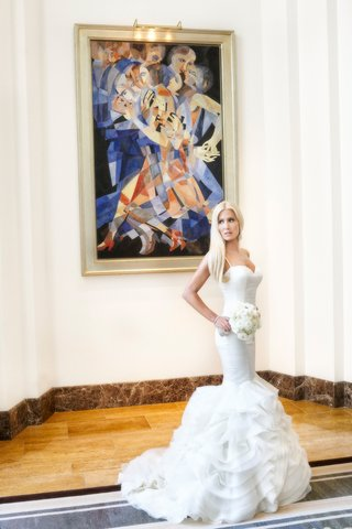 bride-in-rivini-ruffled-mermaid-wedding-dress-in-front-of-abstract-painting