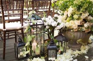 lanterns-with-candles-set-at-flower-petals-behind-chiavari-chairs