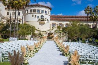 outdoor-wedding-ceremony-monarch-beach-resort-pampas-grass-lining-aisle-runner-white-chairs-rotunda