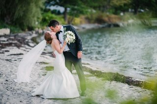 couple-kissing-beach-maine-cape-elizabeth-sand-green-color-palette-wedding-rivini-dress