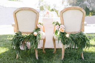 a-couples-chairs-at-their-sweetheart-table-for-their-reception-featuring-lush-greenery-light-flowers