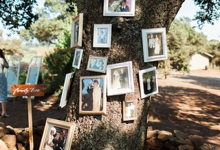 old-family-photos-hanging-on-tree-wedding-ceremony-rustic-bride-groom