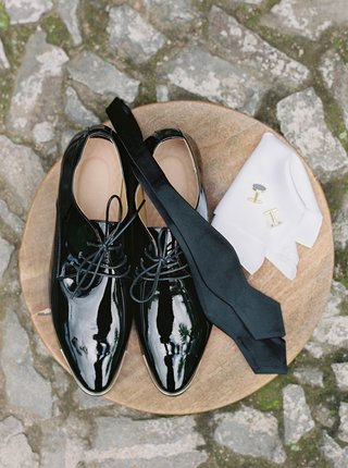 wedding-accessories-for-groom-wood-table-on-cobblestone-street-in-guatemala-patent-leather