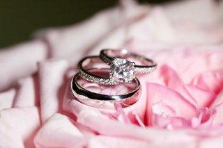 bride-and-grooms-wedding-rings-on-top-of-pink-rose-petals