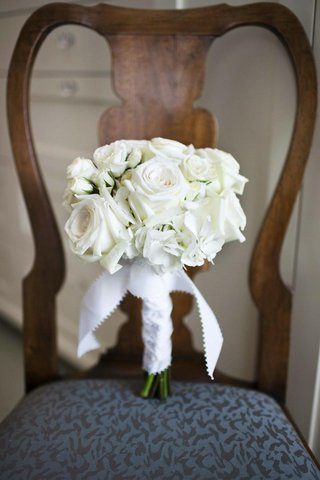 ivory-flowers-wrapped-in-scalloped-ribbon-on-chair