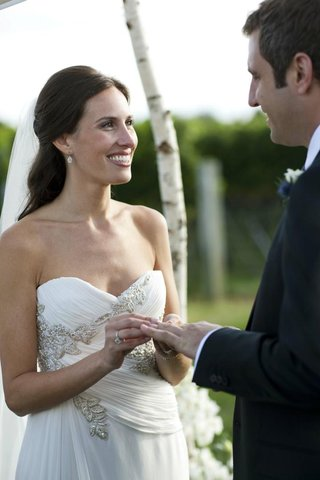 bride-smiling-and-putting-wedding-band-on-husband