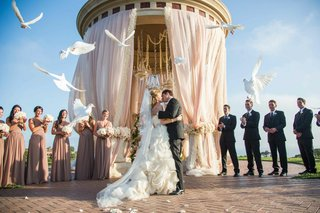 bride-and-groom-kiss-among-flying-doves