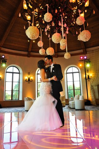 bride-and-groom-kiss-on-pink-dance-floor-under-rose-balls