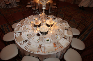 reception-table-with-white-tablecloth-candles-in-crystal-holders-and-arrangements-of-white-roses