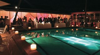 swimming-pool-surrounded-by-candles-and-lit-with-monogram