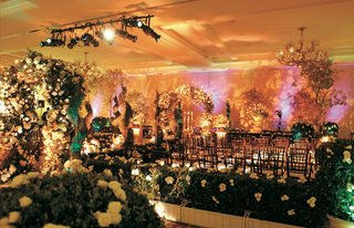 ballroom-decorated-with-bushes-flower-archways-and-ceremony-seating