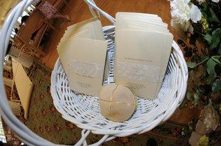 white-basket-holding-ivory-wedding-programs