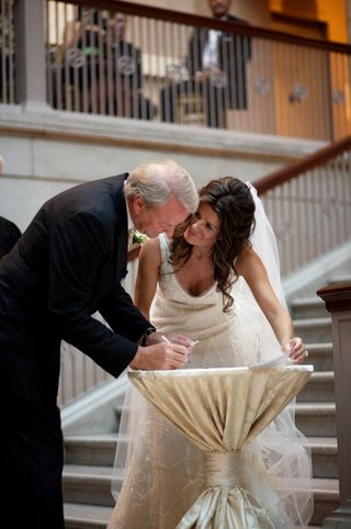 bride-and-groom-sign-paperwork-on-stairs