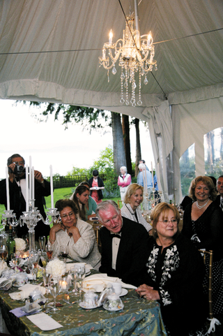 wedding-reception-tented-area-with-chandelier-and-table-decorated-with-crystal-candelabra