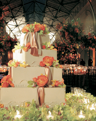 four-tiered-wedding-cake-with-roses-orchids-and-ribbons