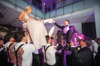 wedding reception bride and groom hoisted up on chairs during hora jewish wedding purple lighting