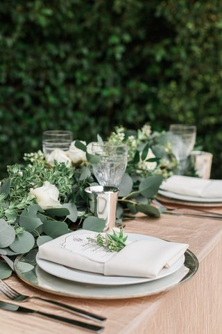 garden-wedding-reception-table-with-greenery-runner-white-roses-golden-tablecloth-charger