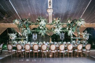 wedding-reception-head-table-wood-chairs-greenery-flower-chandelier-tent-string-lights-candelabra