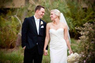 newlyweds-holding-hands-in-garden