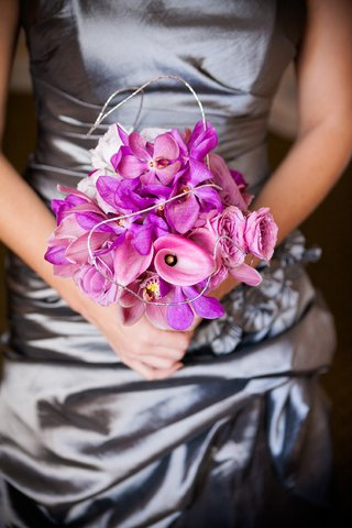 bridesmaid-in-silver-holding-nosegay-of-orchids