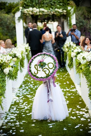 flower-girl-walking-down-grass-aisle-holding-umbrella