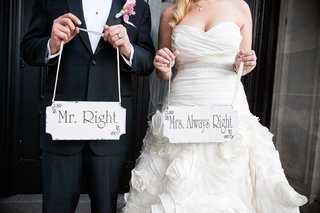 bride-and-groom-holding-personalized-wood-signs