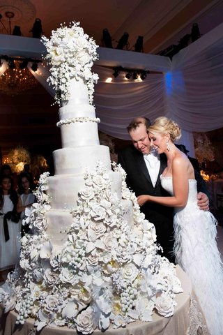 bride-in-a-strapless-gown-with-groom-in-a-black-tuxedo-cuts-cake-decorated-with-sugar-flowers