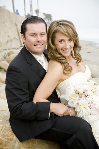 bride-and-groom-smile-on-rocky-beach