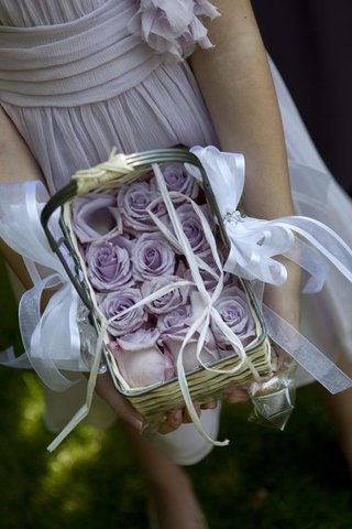 flower-girl-holds-wicker-basket-filled-with-purple-roses
