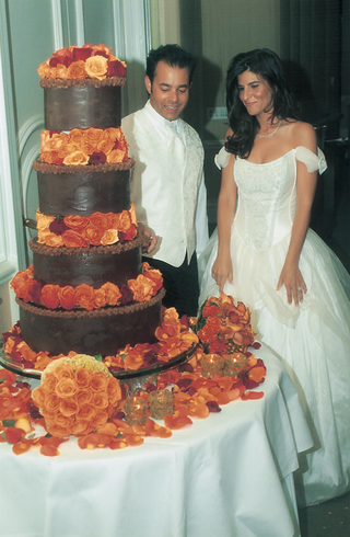 four-tiered-cake-with-brown-frosting-and-orange-roses