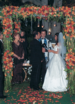 ceremony-under-chuppah-decorated-with-orange-flowers-and-greenery