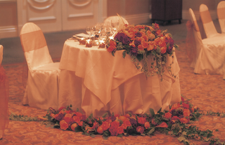 sweetheart-table-covered-in-white-linens-and-orange-flowers