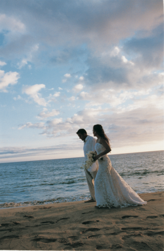bride-and-groom-walk-across-the-sand-next-to-the-ocean