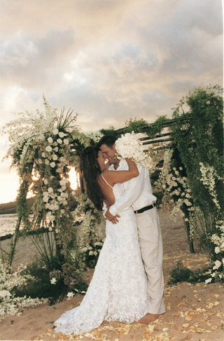 bride-and-groom-kiss-in-front-of-chuppah-decorated-with-greenery-and-white-flowers