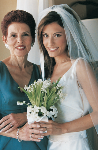 bride-and-her-mom-hold-the-bouquet-together