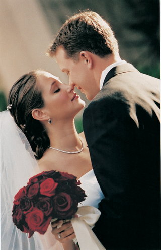 bride-eskimo-kisses-groom-holding-red-flowers