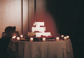 wedding-cake-surrounded-by-roses-and-candles