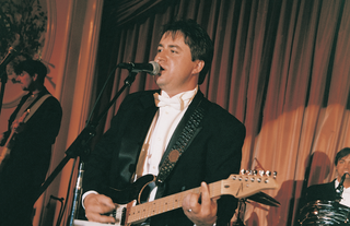 formal-groom-on-stage-with-electric-guitar-in-tuxedo