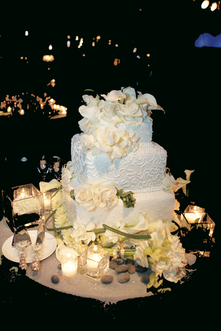 three-layer-cake-surrounded-by-flowers-and-candles