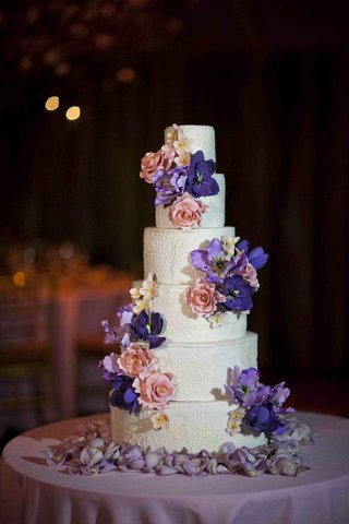 white-wedding-cake-with-textured-surface-decorated-with-pink-and-purple-flowers