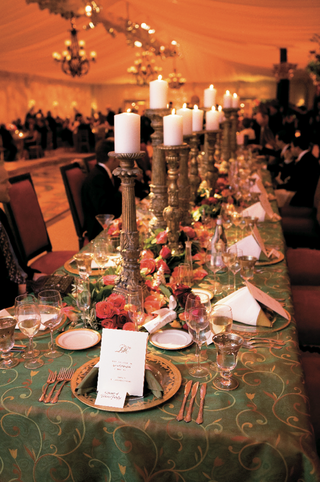 wedding-reception-table-with-green-embroidered-tablecloth-and-white-candles-on-golden-candleholders