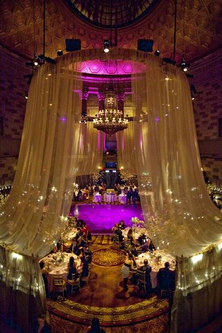 wedding-reception-draped-in-fabric-with-purple-and-gold-lights-at-the-grand-ballroom-of-gotham-hall