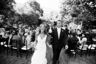 black-and-white-photo-of-a-bride-in-a-monique-lhuillier-gown-and-a-groom-in-a-black-tuxedo-and-tie