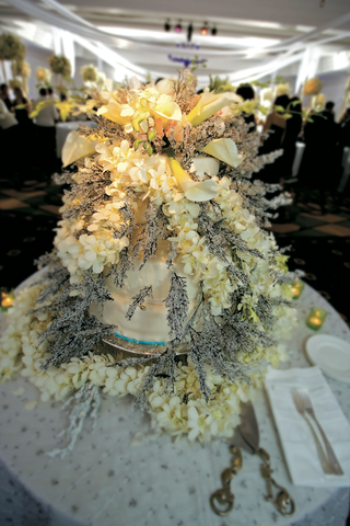 wedding-cake-covered-in-flowers-and-frosted-twigs