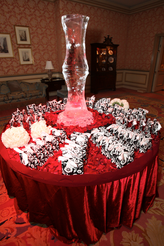 wedding-favor-table-with-ice-sculpture-red-velvet-tablecloth-and-rose-petals