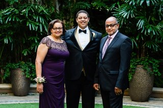 wedding photo of groom with mom in purple dress and dad in purple tie and shirt beverly hills