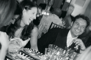 black-and-white-photo-of-bride-and-groom-sitting-at-a-reception-table