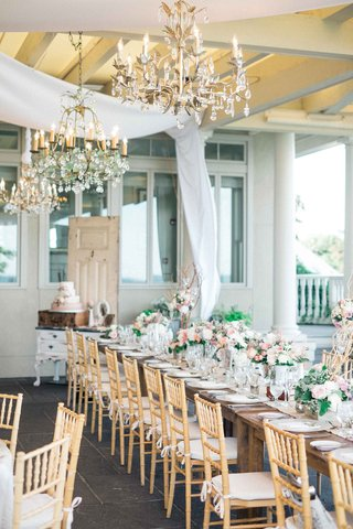 long-tables-with-low-floral-arrangements-in-light-pastel-colors-and-gold-chairs-under-chandeliers