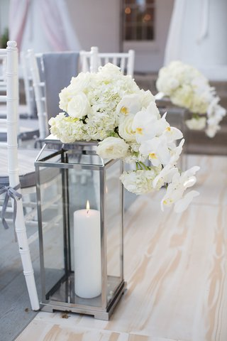 silver-lantern-with-candle-inside-decorated-with-white-hydrangea-rose-and-orchid-flowers-ceremony