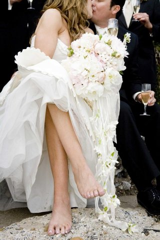 barefoot-bride-and-groom-kiss-while-holding-champagne